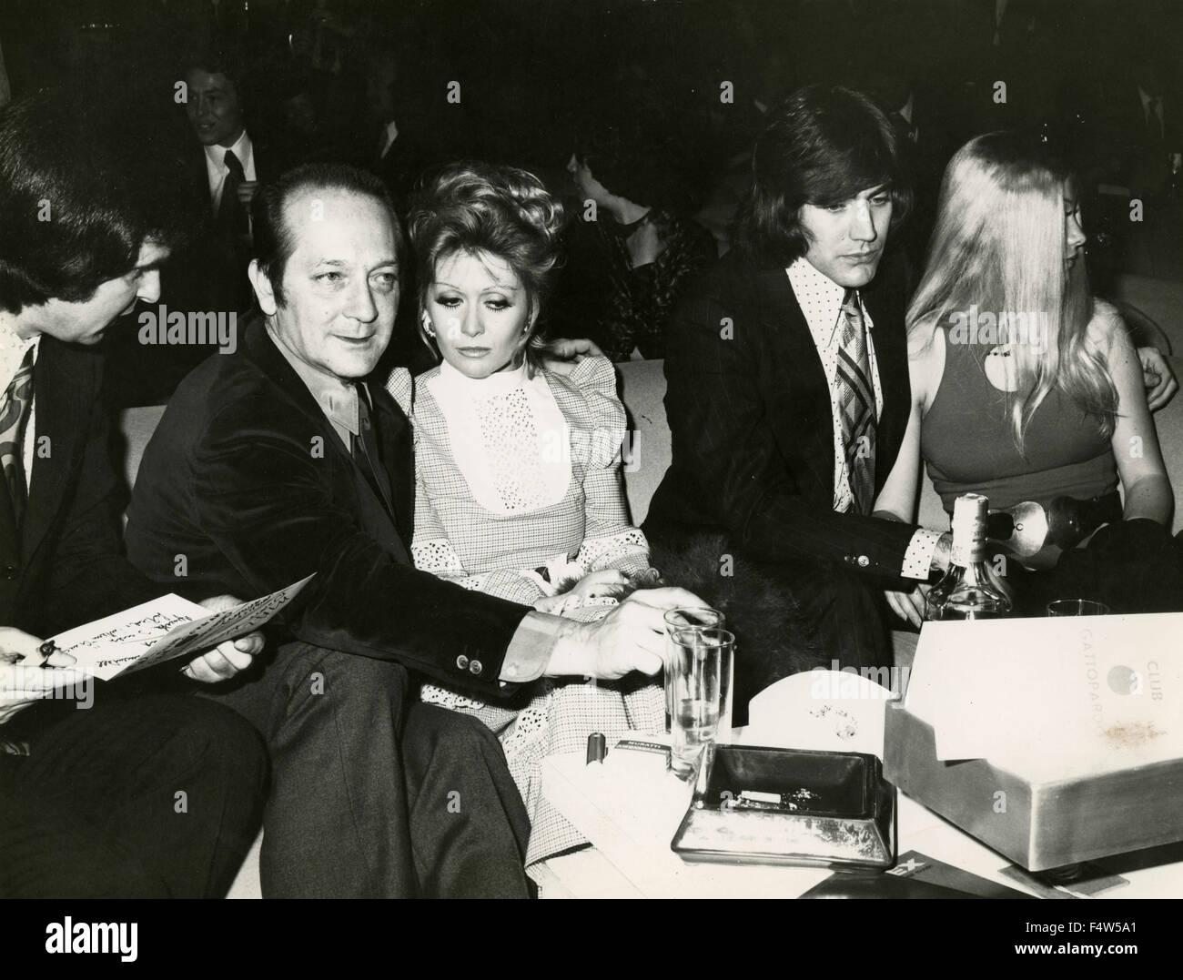 """Le chanteur Mal des primitives avec des amis à une table dans la discothèque """"Il Gattopardo"""", Photo Stock"""