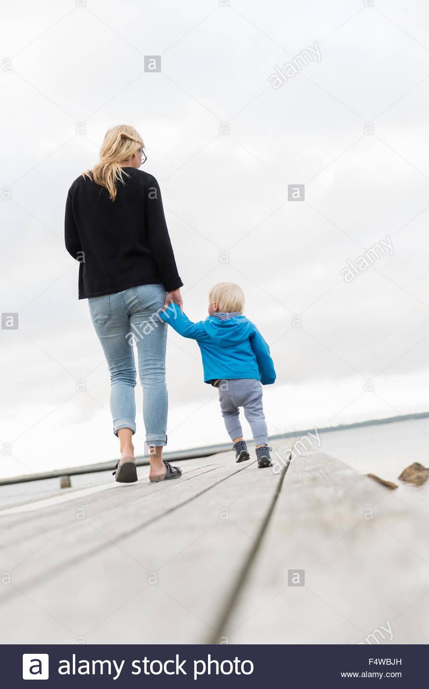 La Suède, Gotland, Farosund, mère avec son (12-17 mois) on jetty Photo Stock