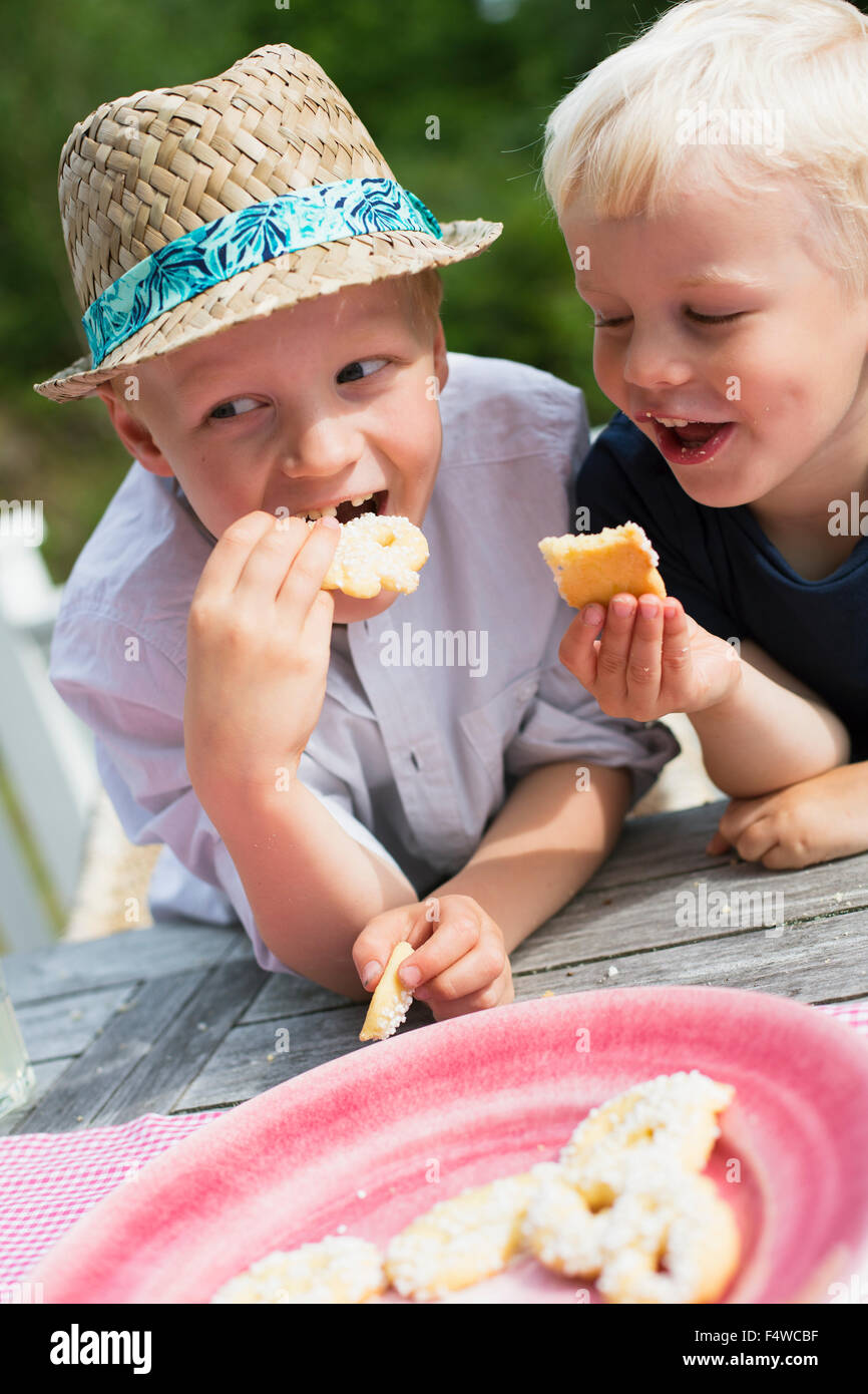 Deux garçons (4-5, 6-7) eating cookies Photo Stock