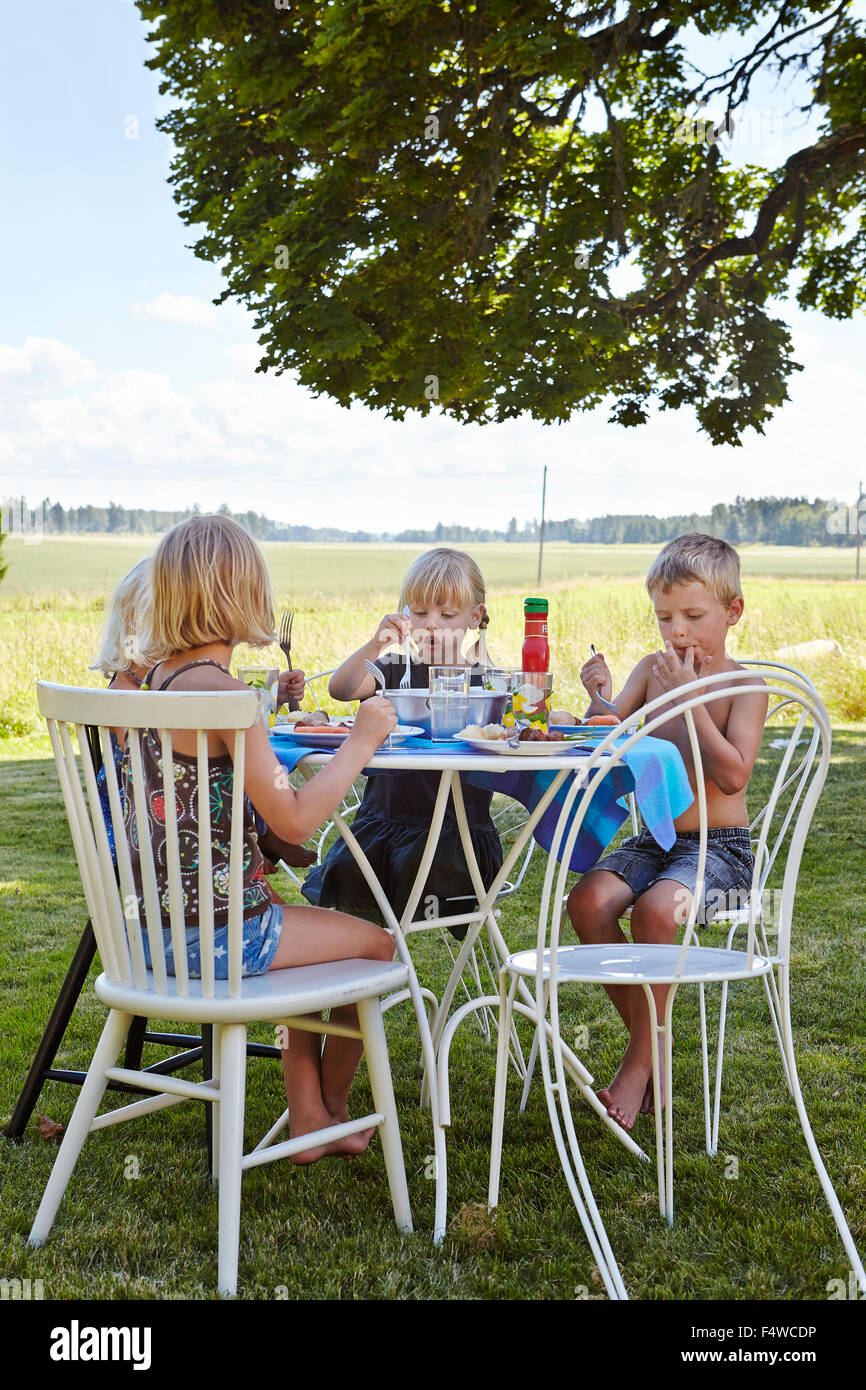 Enfants (4-5, 6-7) eating lunch in meadow Photo Stock