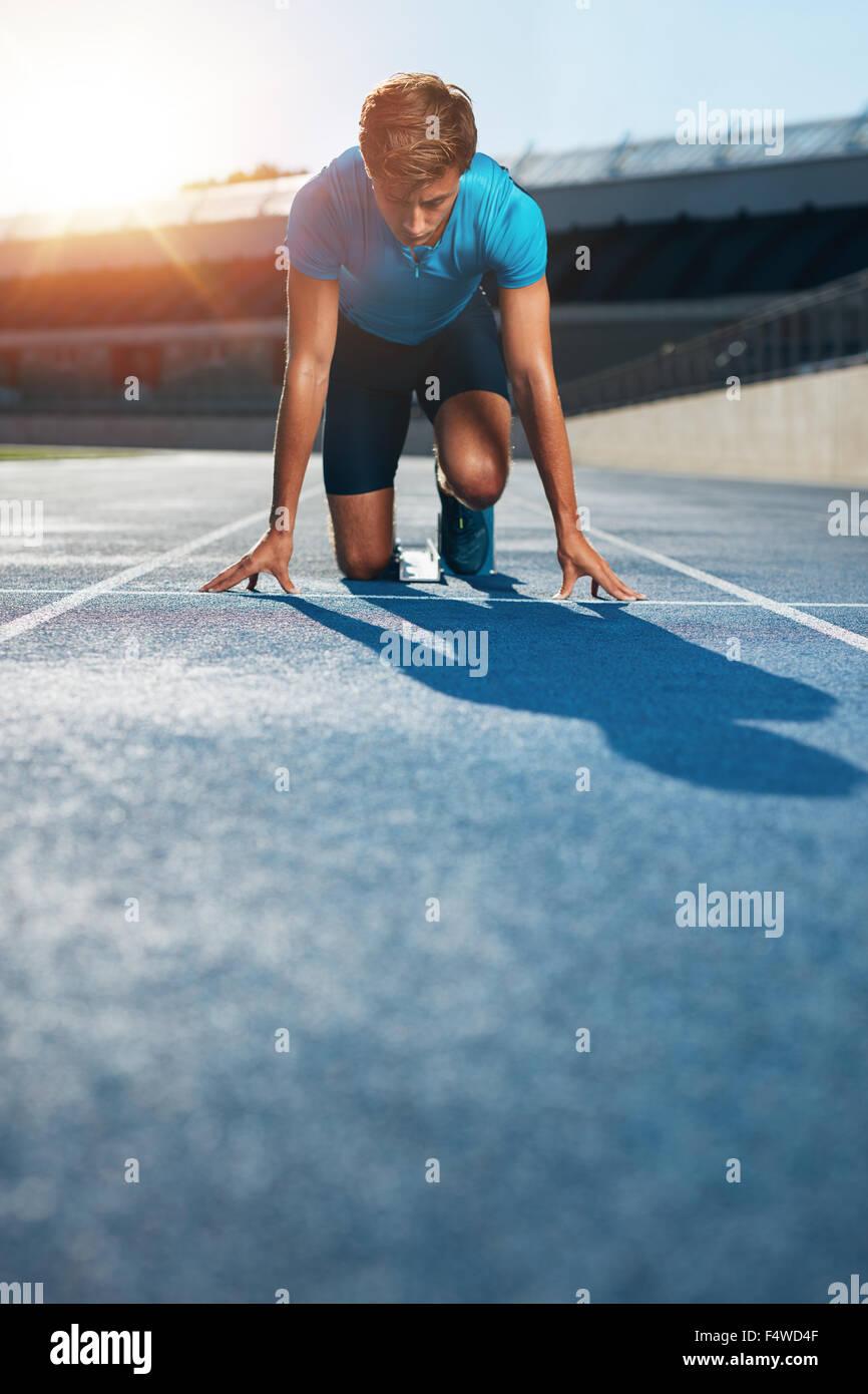 Athlète masculin professionnel en position sur le sprint de blocs d'une piste de course dans le stade d'athlétisme. Photo Stock