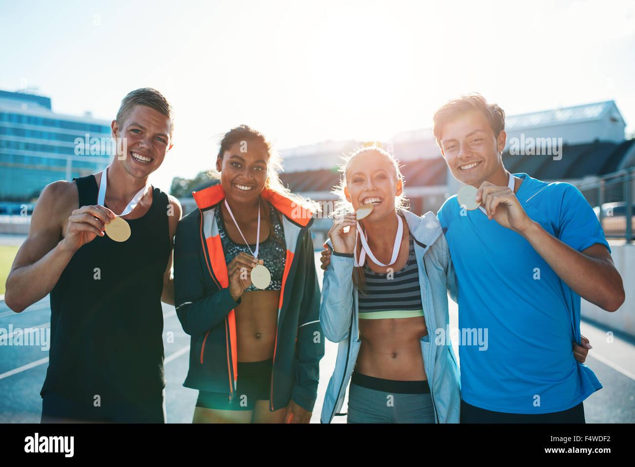 Portrait de jeunes coureurs extatique montrant des médailles. Les jeunes hommes et femmes à la hâte Photo Stock