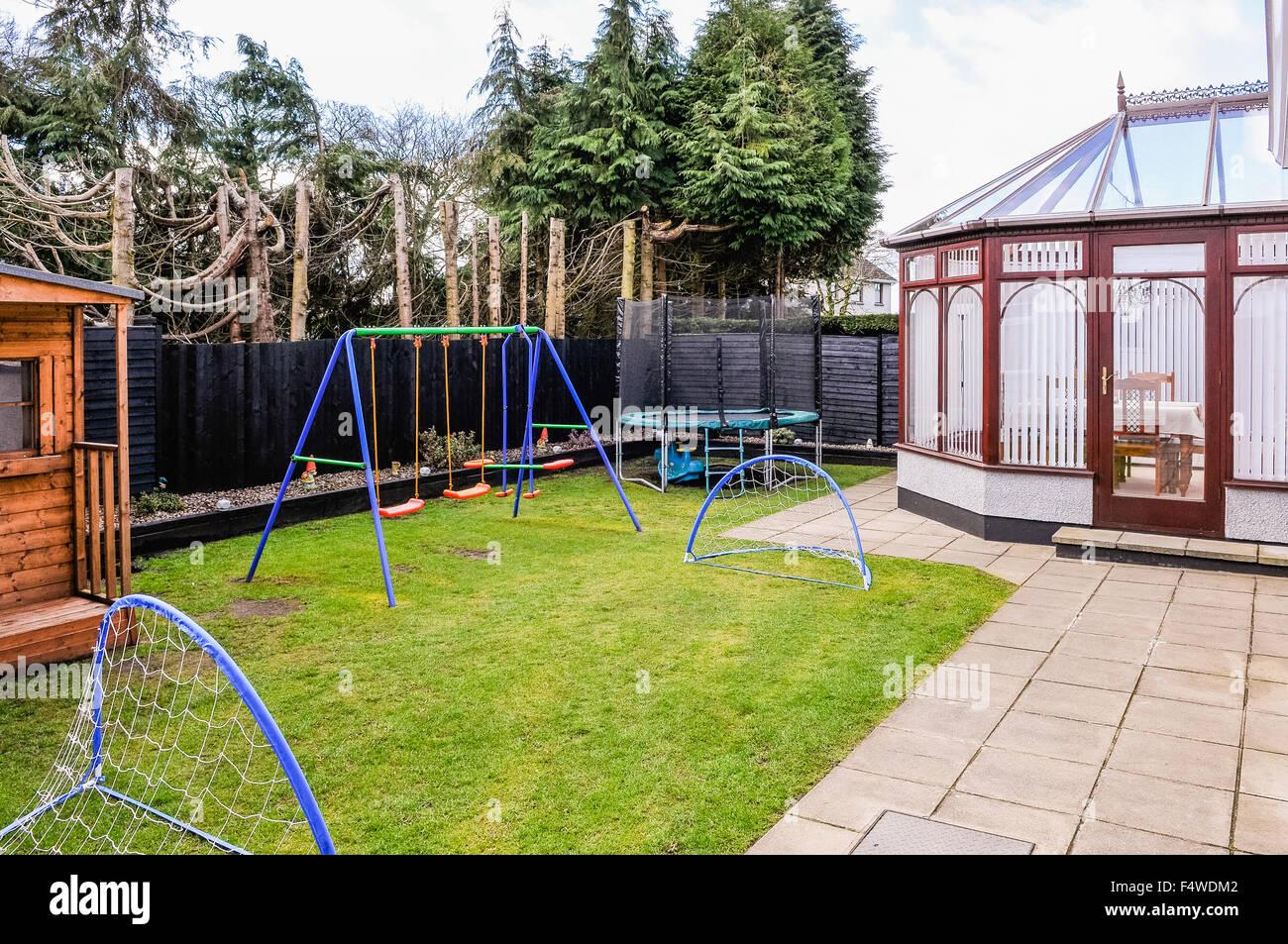 Jardin arrière familial clos avec balançoires pour enfants ...