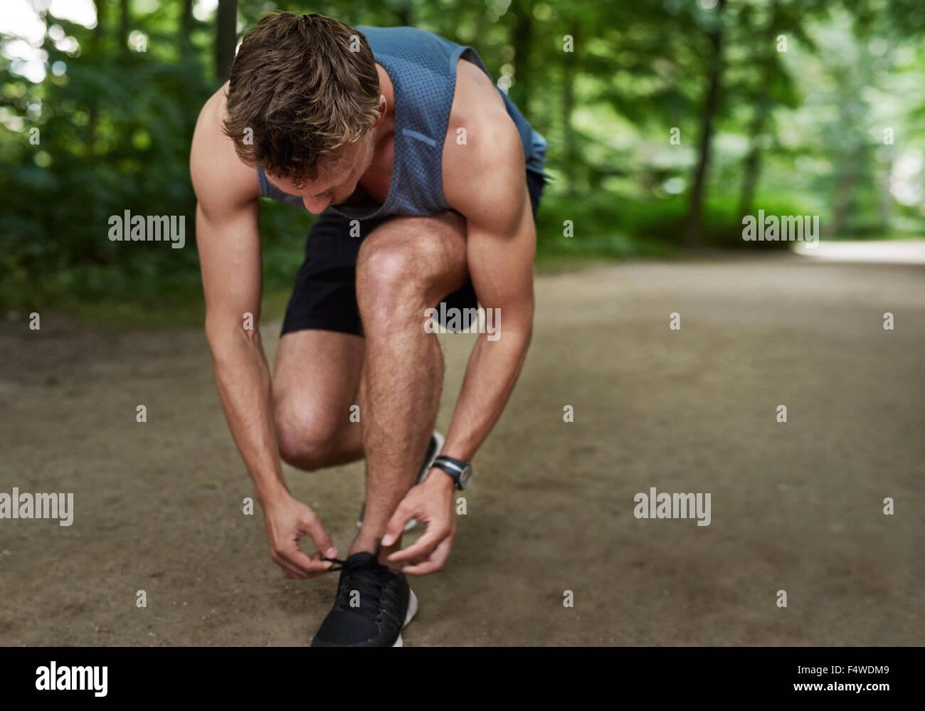 Mettre en place l'homme jogger se pencher lier ses lacets dans une piste à travers un parc boisé luxuriant dans un concept de vie sain Banque D'Images