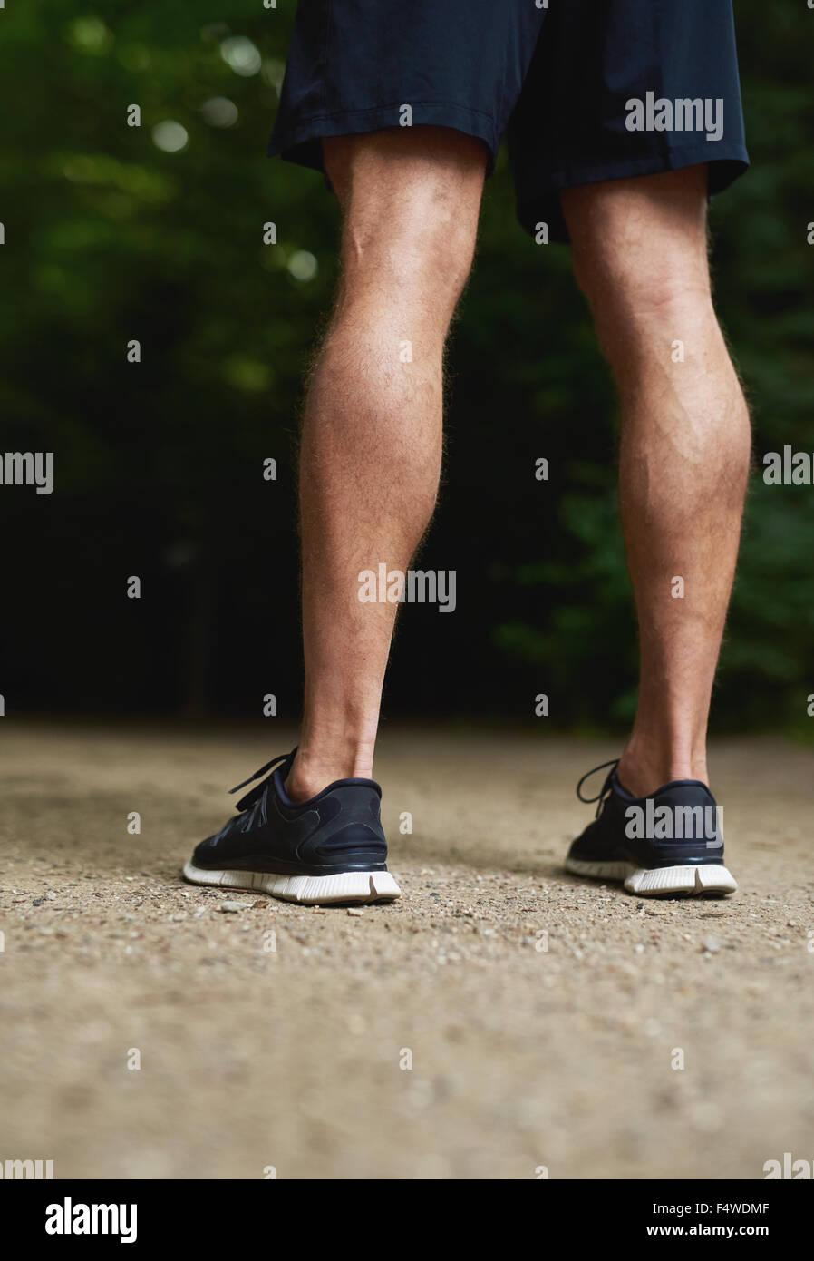 Vue arrière des jambes d'un homme athlétique musclé fit avec les veaux aux couleurs à l'extérieur Photo Stock