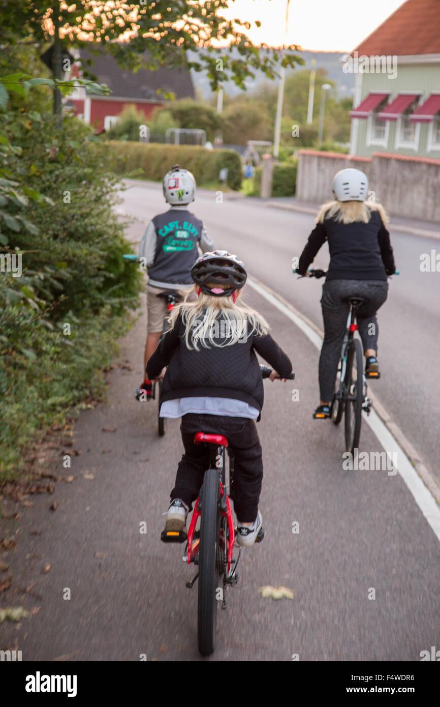 Mère et enfants (10-11, 12-13) randonnée à vélo sur la rue Photo Stock