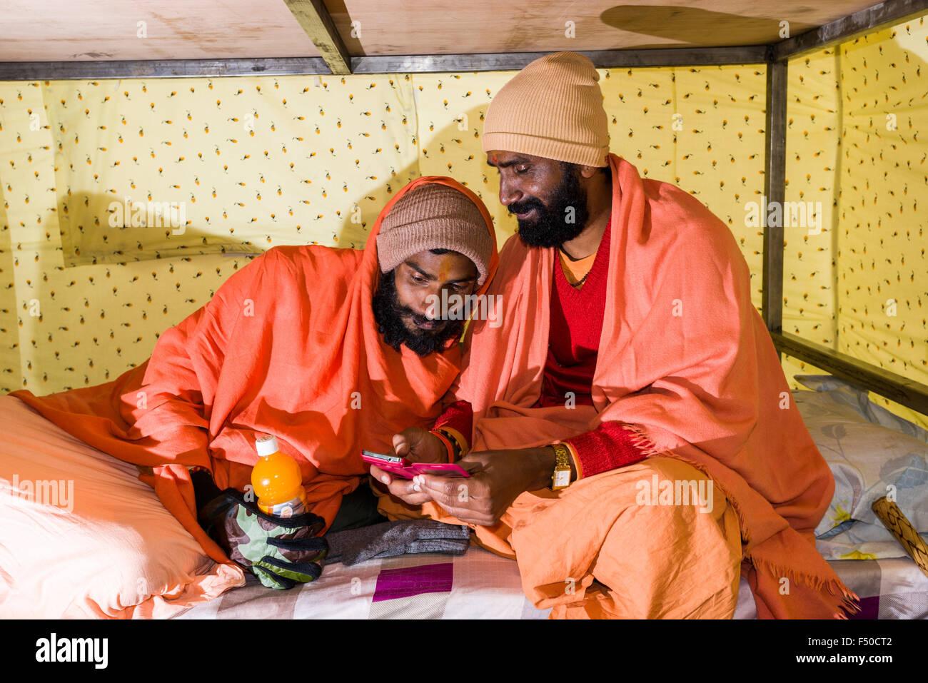 Deux sadhus, saints hommes, jouent avec un smartphone dans une tente Banque D'Images