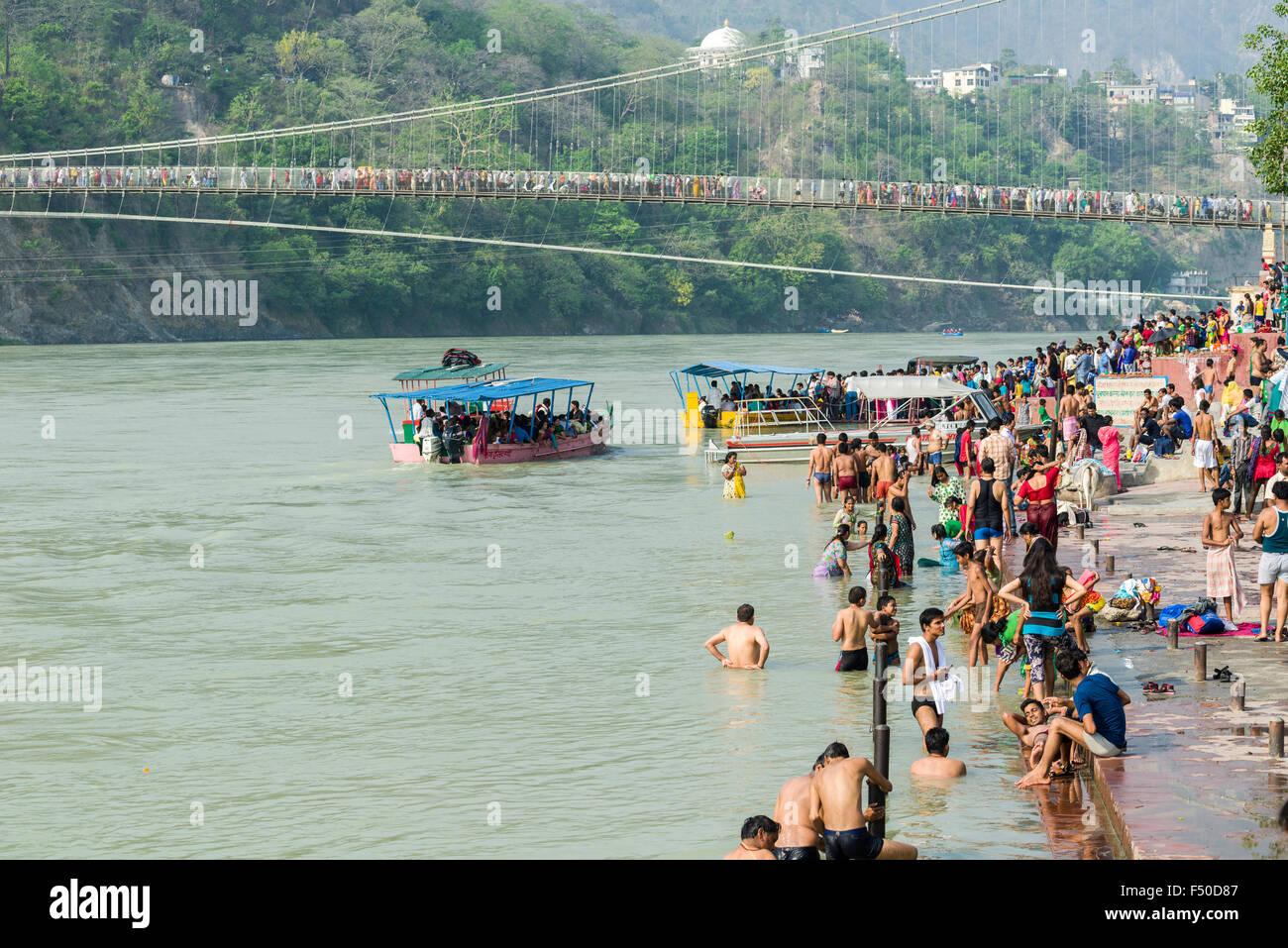Les pèlerins sont en baignoire sur les rives de la fleuve saint Ganges, le pont ram jhula et d'un traversier dans Banque D'Images