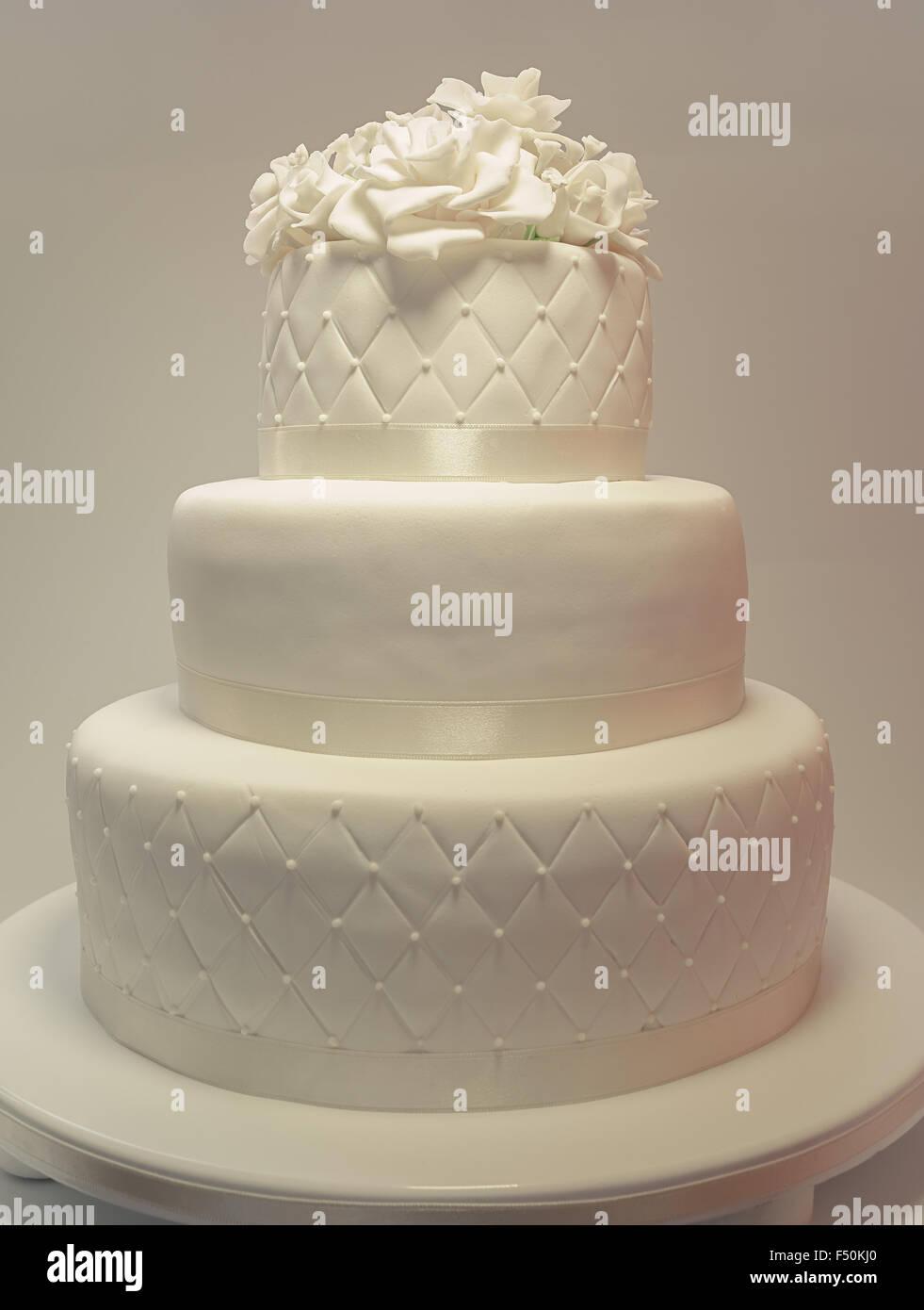 Détails d'un gâteau de mariage, décoration avec fondant blanc sur fond blanc. Photo Stock