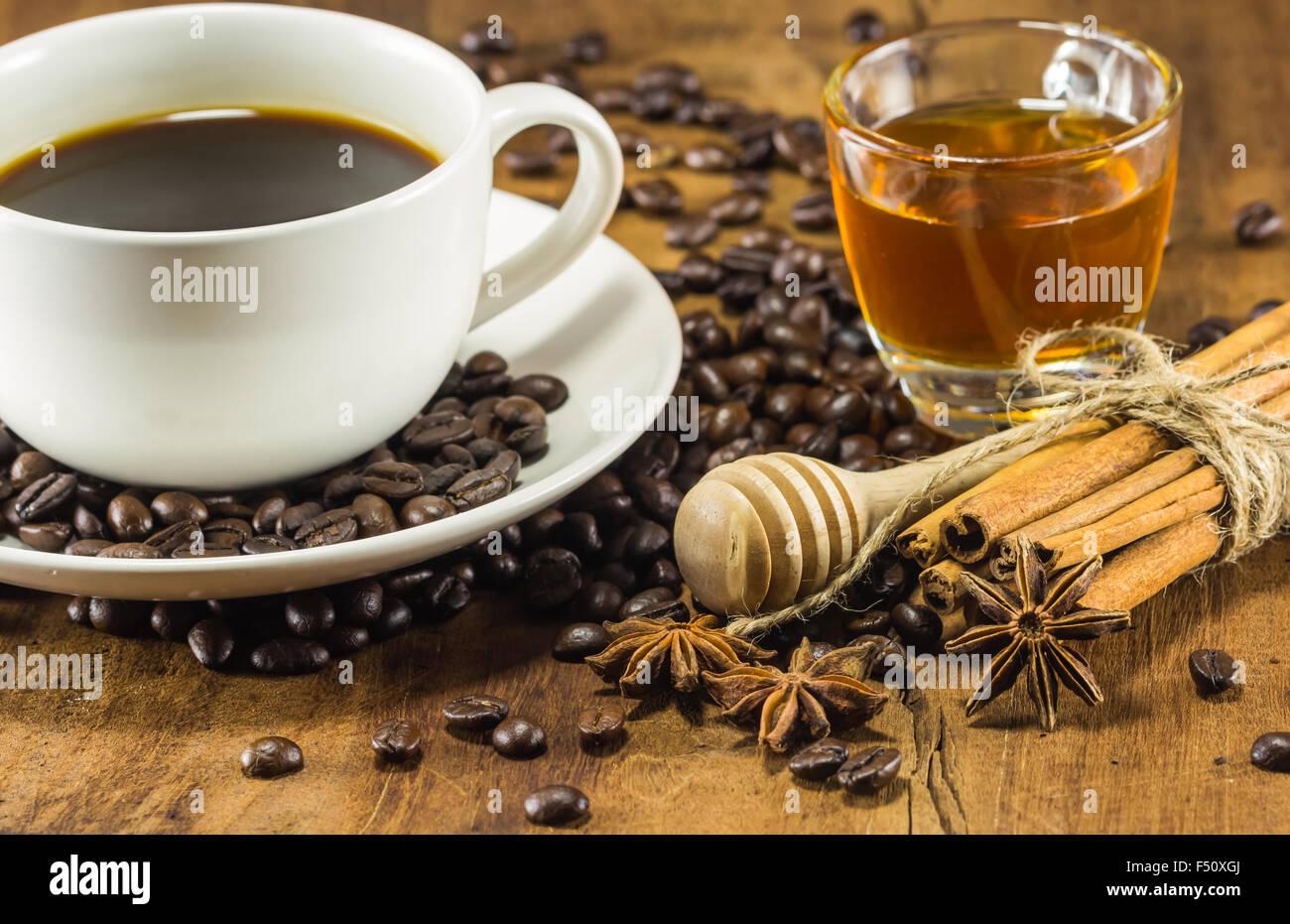 Café sur la tasse avec les grains de café, de miel et de cannelle sur fond de bois chaud, tonification, selective Banque D'Images