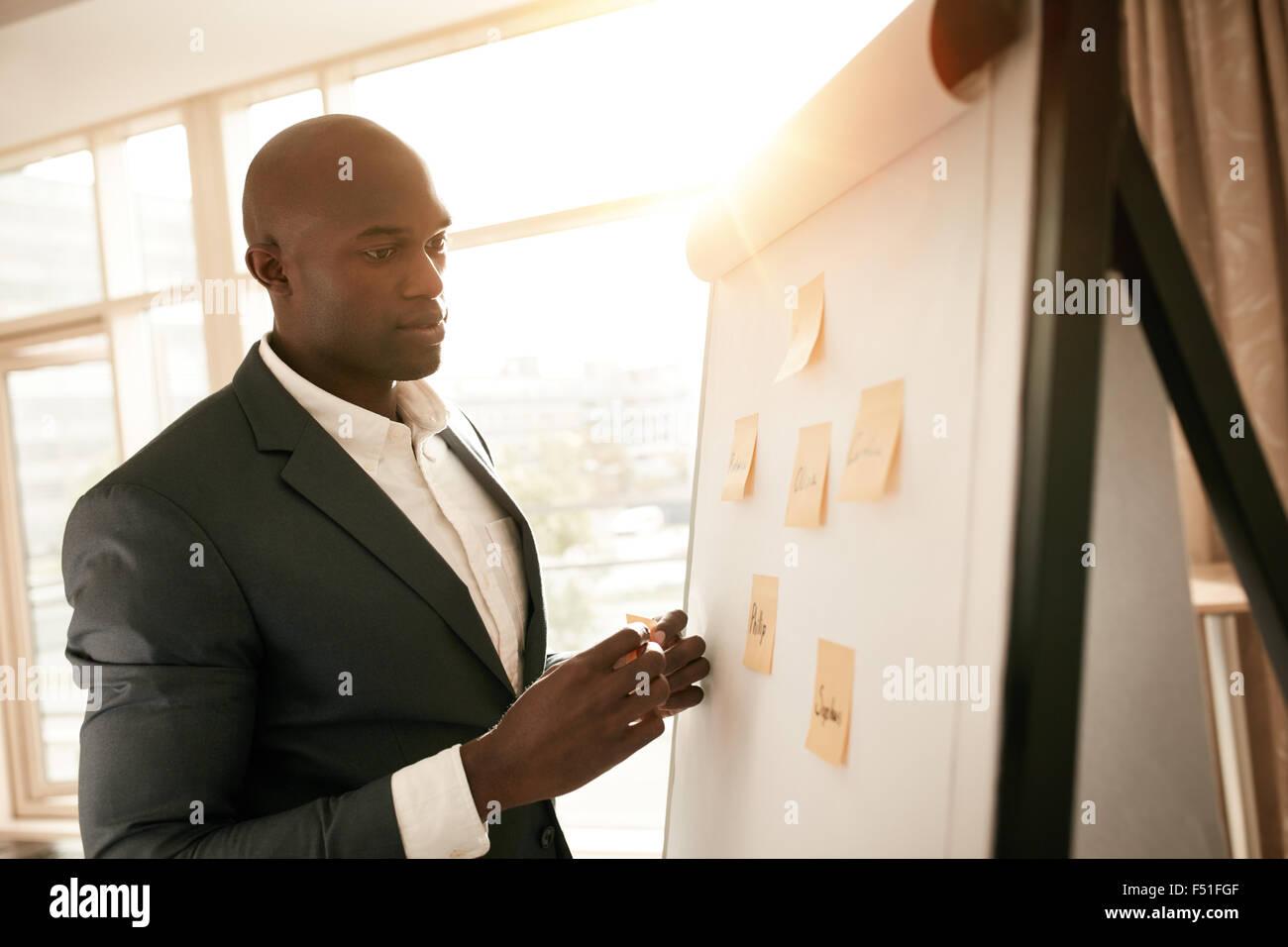 Portrait de l'Afrique par un tableau blanc avec des notes autocollantes. Jeune Chef d'entreprise présentant Photo Stock
