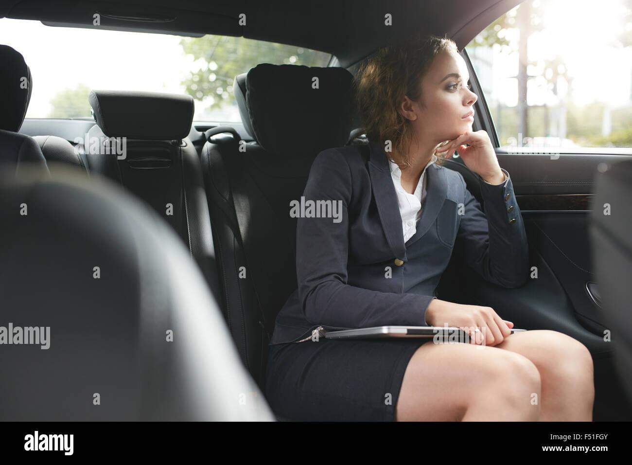 Young businesswoman pour se rendre au travail et dans la voiture de luxe sur le siège arrière à l'extérieur Photo Stock