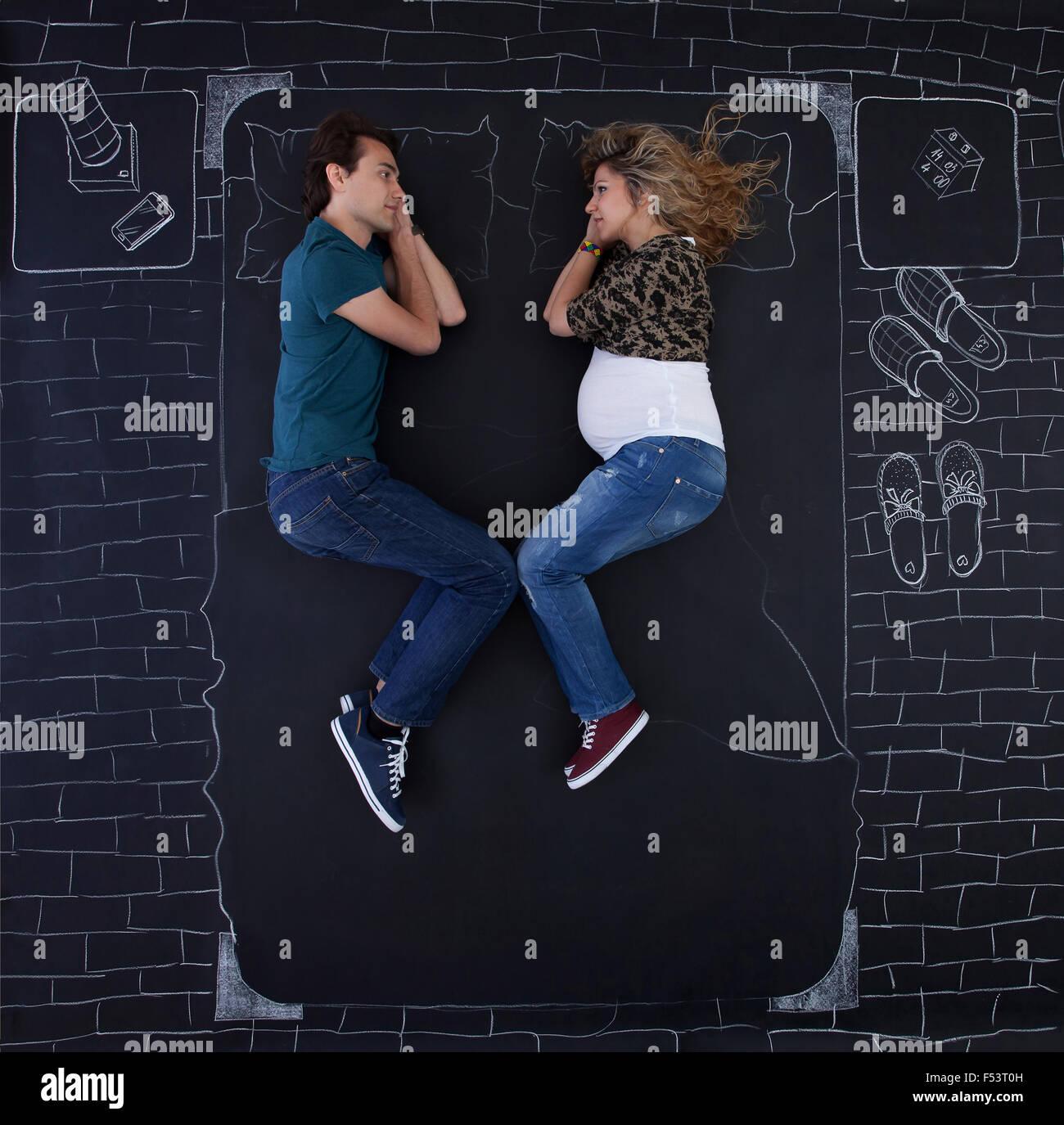 Jeune couple détendre dans un lit drawed par la craie sur papier. Photo Stock