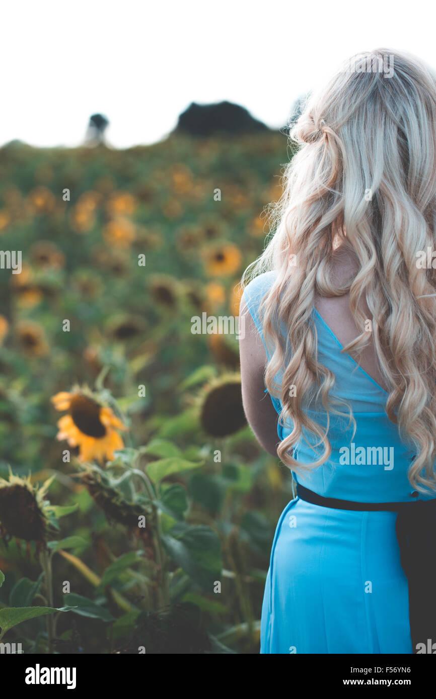 Belle jeune femme dans un champ de tournesol à l'heure d'or Photo Stock