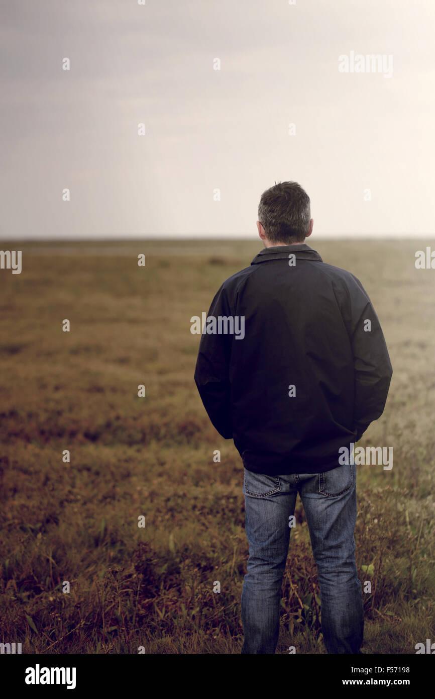 Bel homme d'âge moyen marche à travers une zone côtière rurale Photo Stock