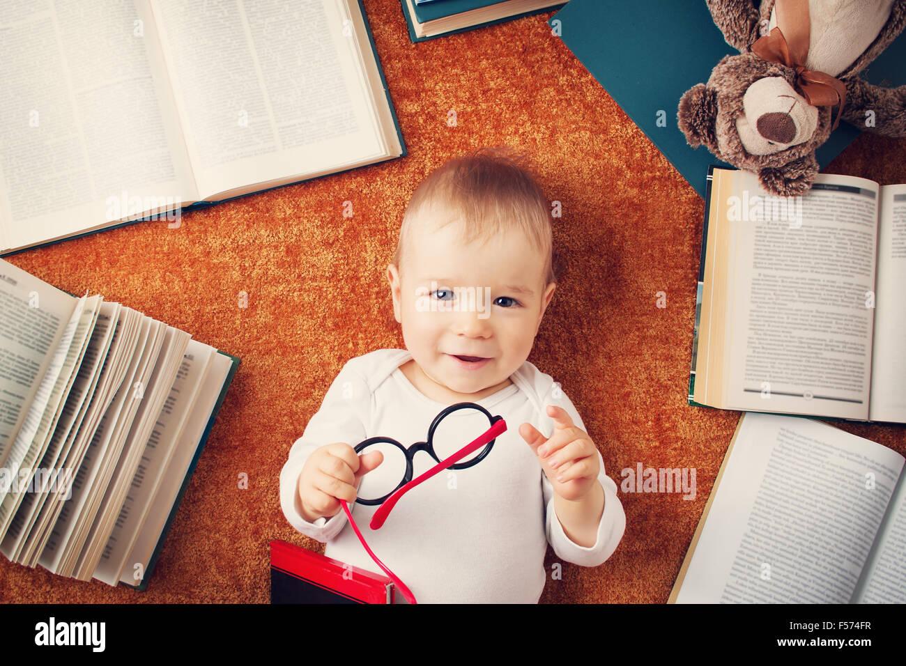 Un an bébé avec spectackles et un ours en peluche Photo Stock