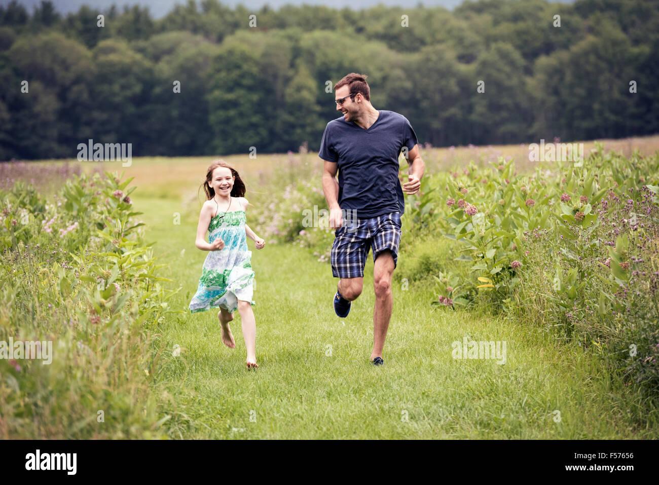 Un homme et un jeune enfant qui traverse une prairie de fleurs sauvages. Photo Stock