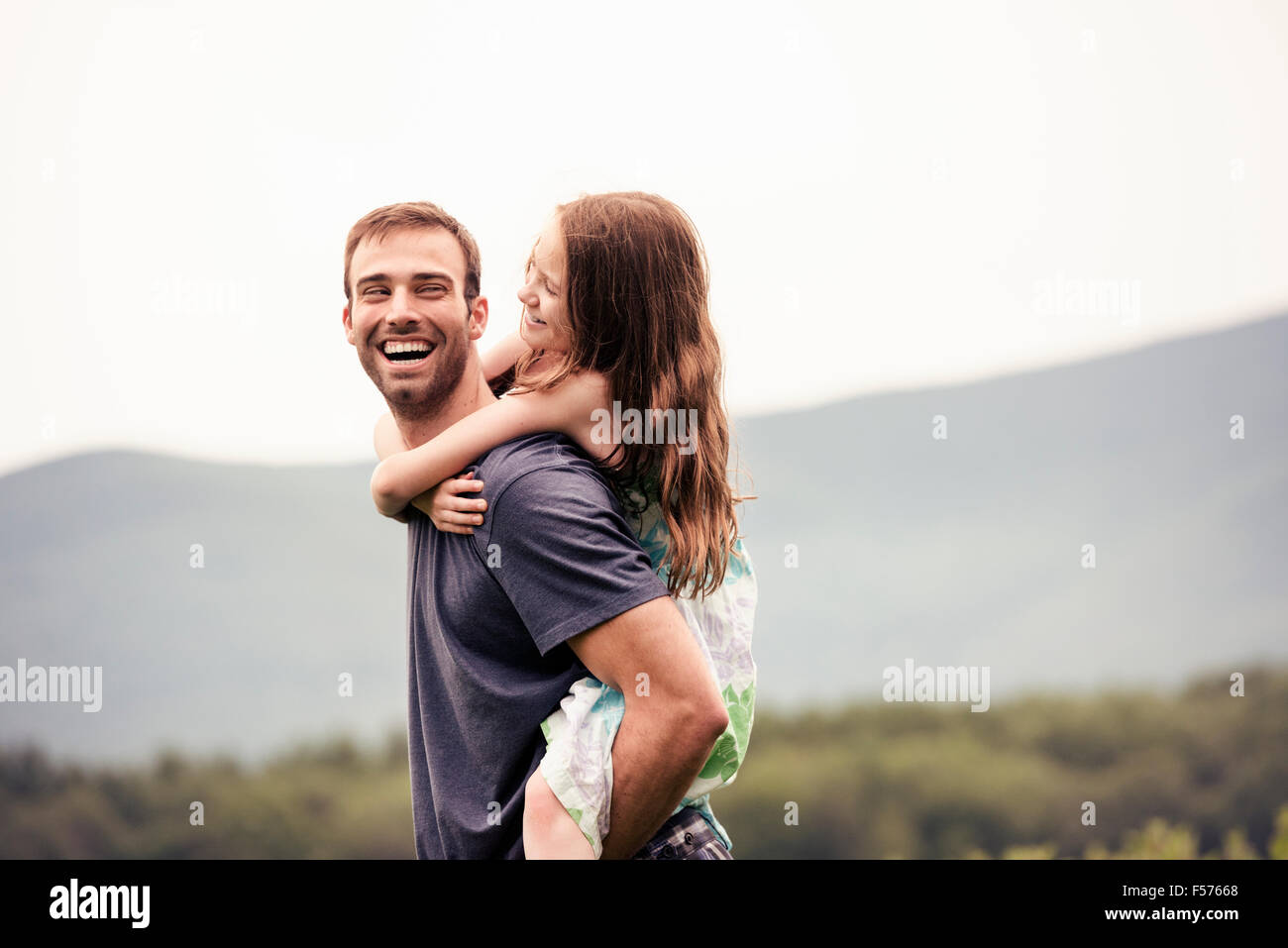 Un homme donnant à un jeune enfant un dans un pré. Photo Stock
