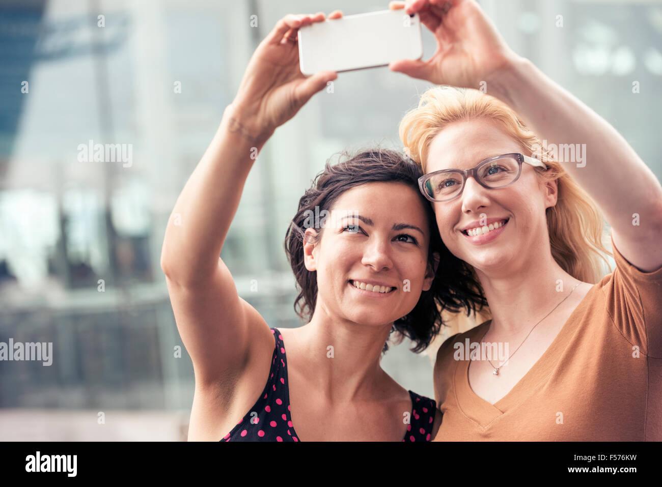 Deux femmes sur une rue de la ville, en tenant un téléphone intelligent avec un selfies. Photo Stock