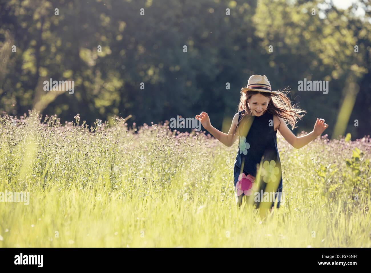 Un enfant, une jeune fille en chapeau de paille dans un pré de fleurs sauvages en été. Photo Stock
