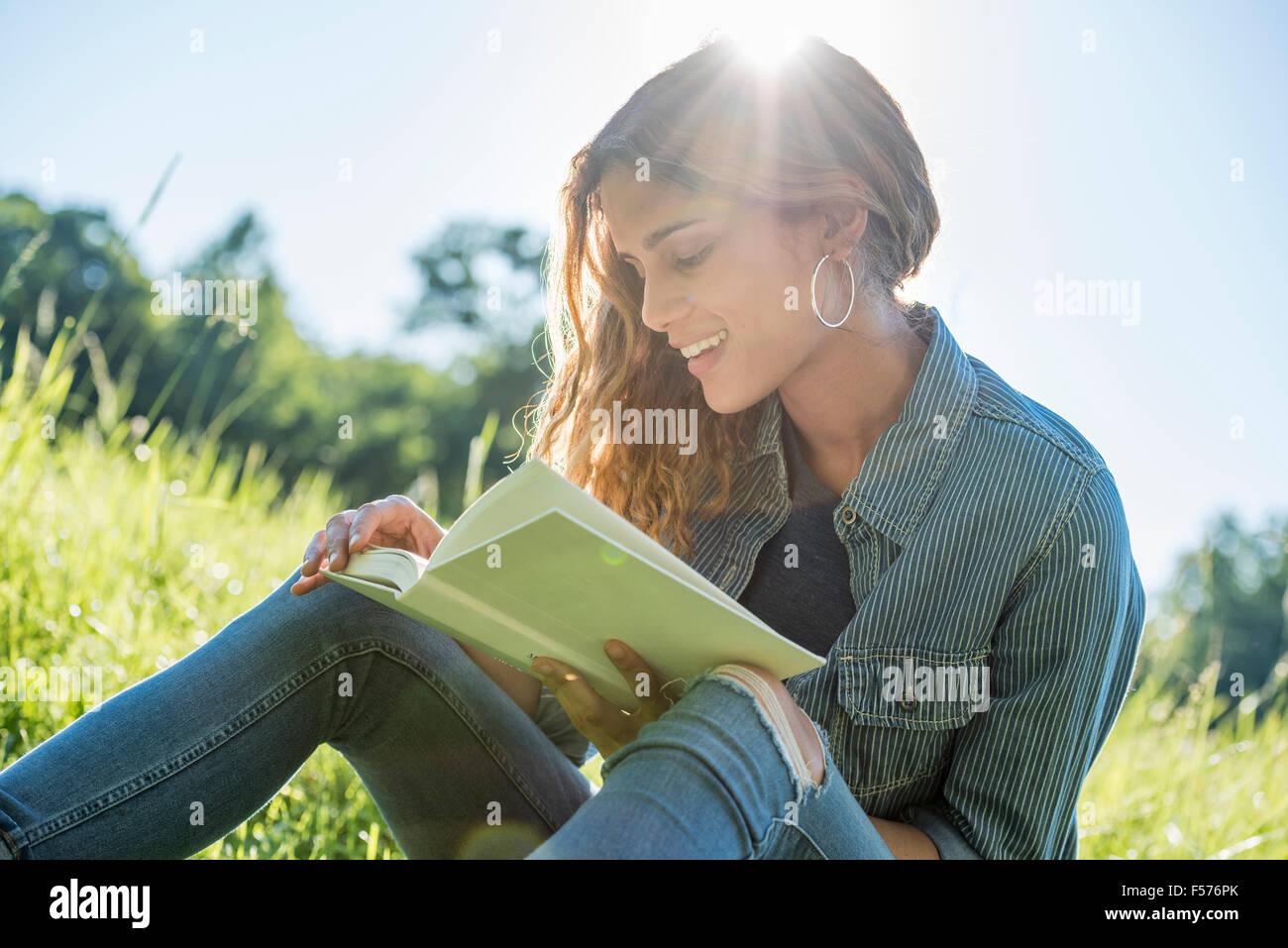 Une jeune femme assise au soleil en lisant un livre Photo Stock
