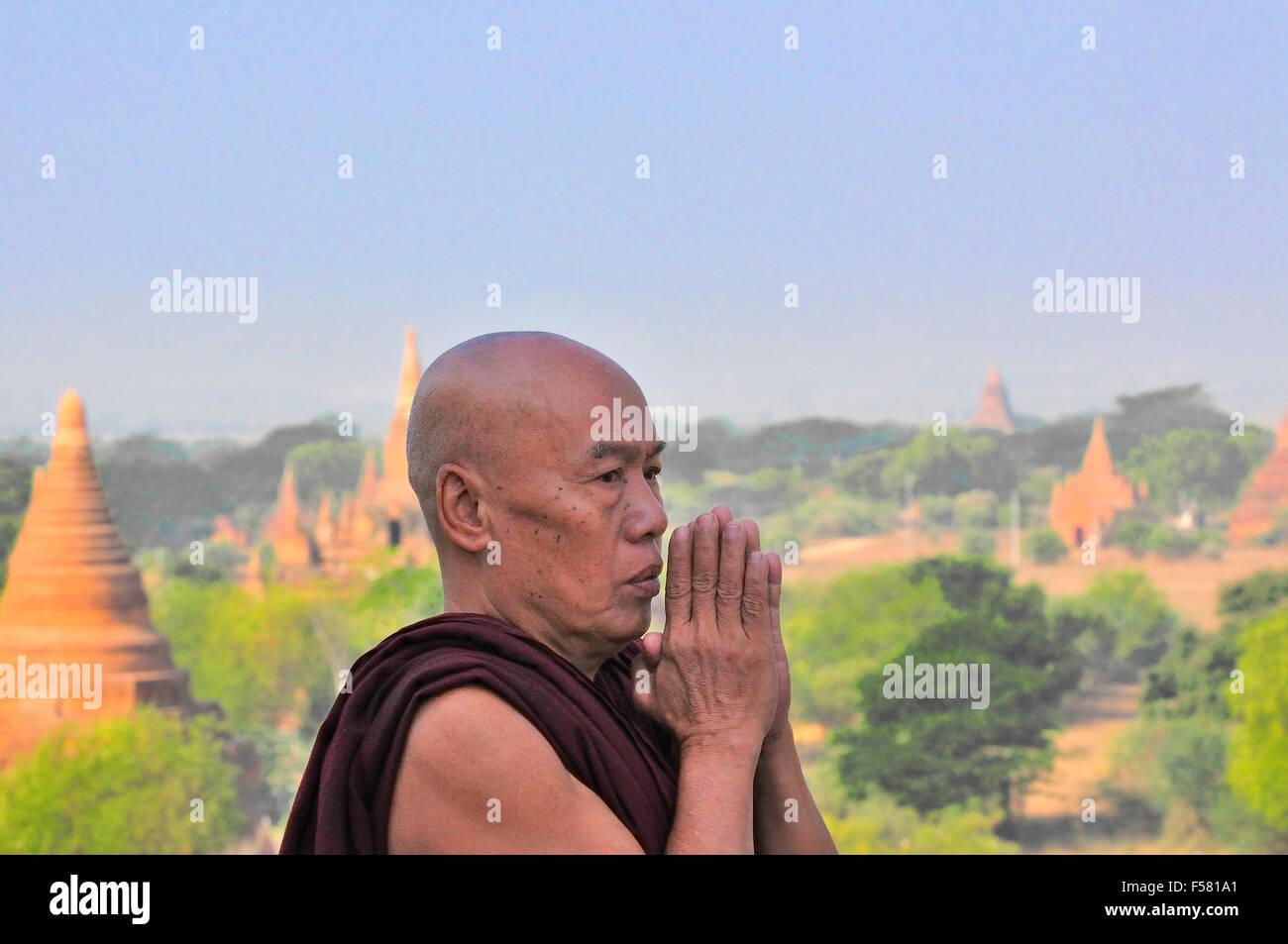 Le moine bouddhiste priant sur le haut de la Pagode Shwesandaw à Bagan, Birmanie (Myanmar) Photo Stock