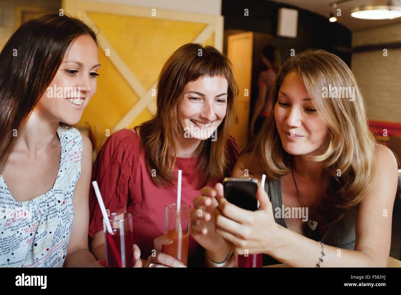 Amis parler dans le café et en regardant les photos sur smart phone Banque D'Images