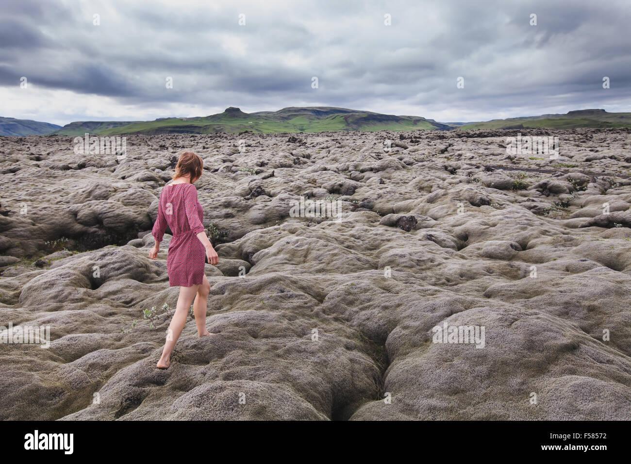 Fashion femme marchant pieds nus dans les champs de lave en Islande Photo Stock