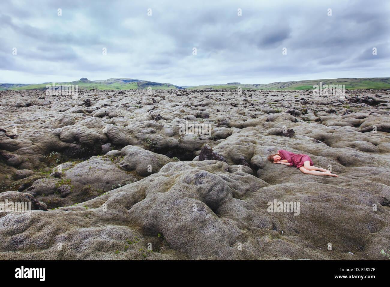 Belle jeune fille en robe rouge dormant dans champ de lave en Islande, la solitude concept Photo Stock