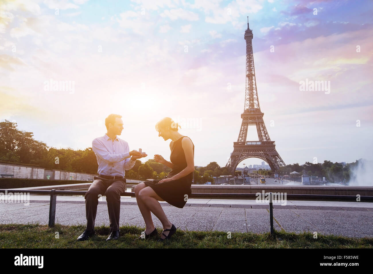 M'épouser, proposition à la Tour Eiffel à Paris, de belles silhouettes de young caucasian couple Photo Stock