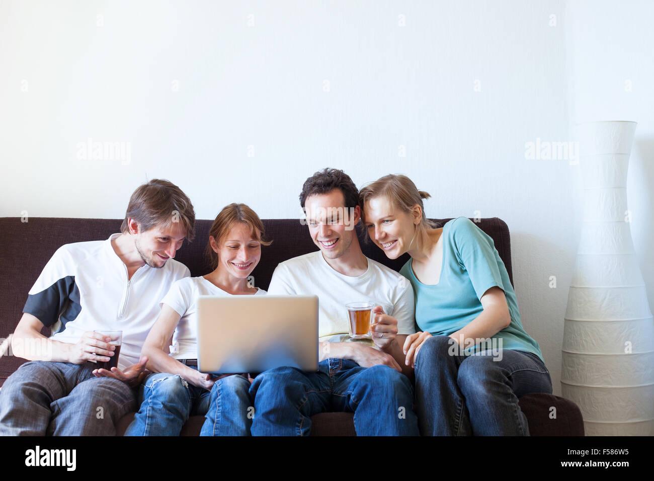 Groupe d'amis, regarder la télévision et smiling Photo Stock