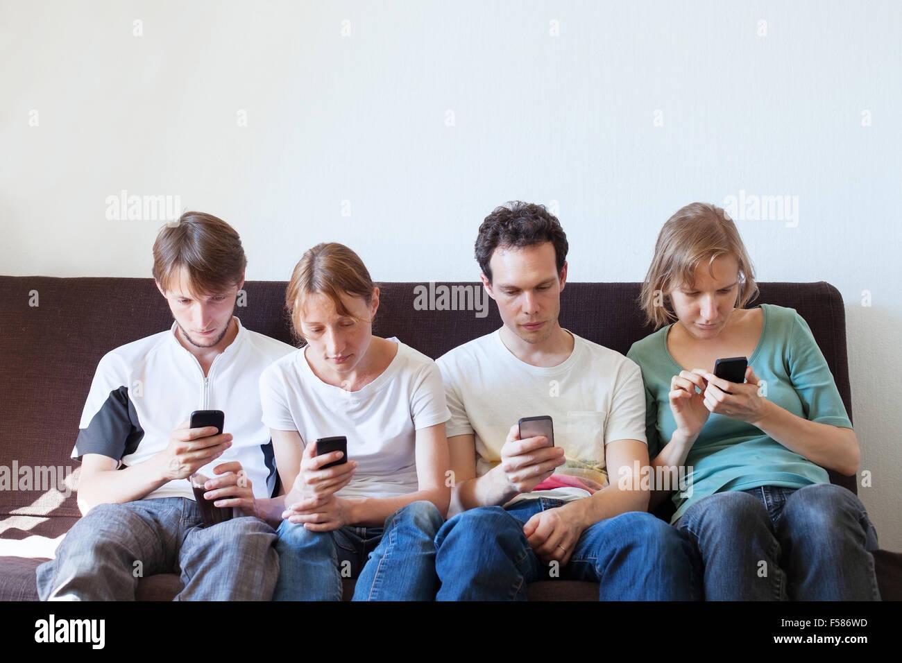 La dépendance à internet, groupe de jeunes à la recherche de leurs téléphones intelligents Banque D'Images