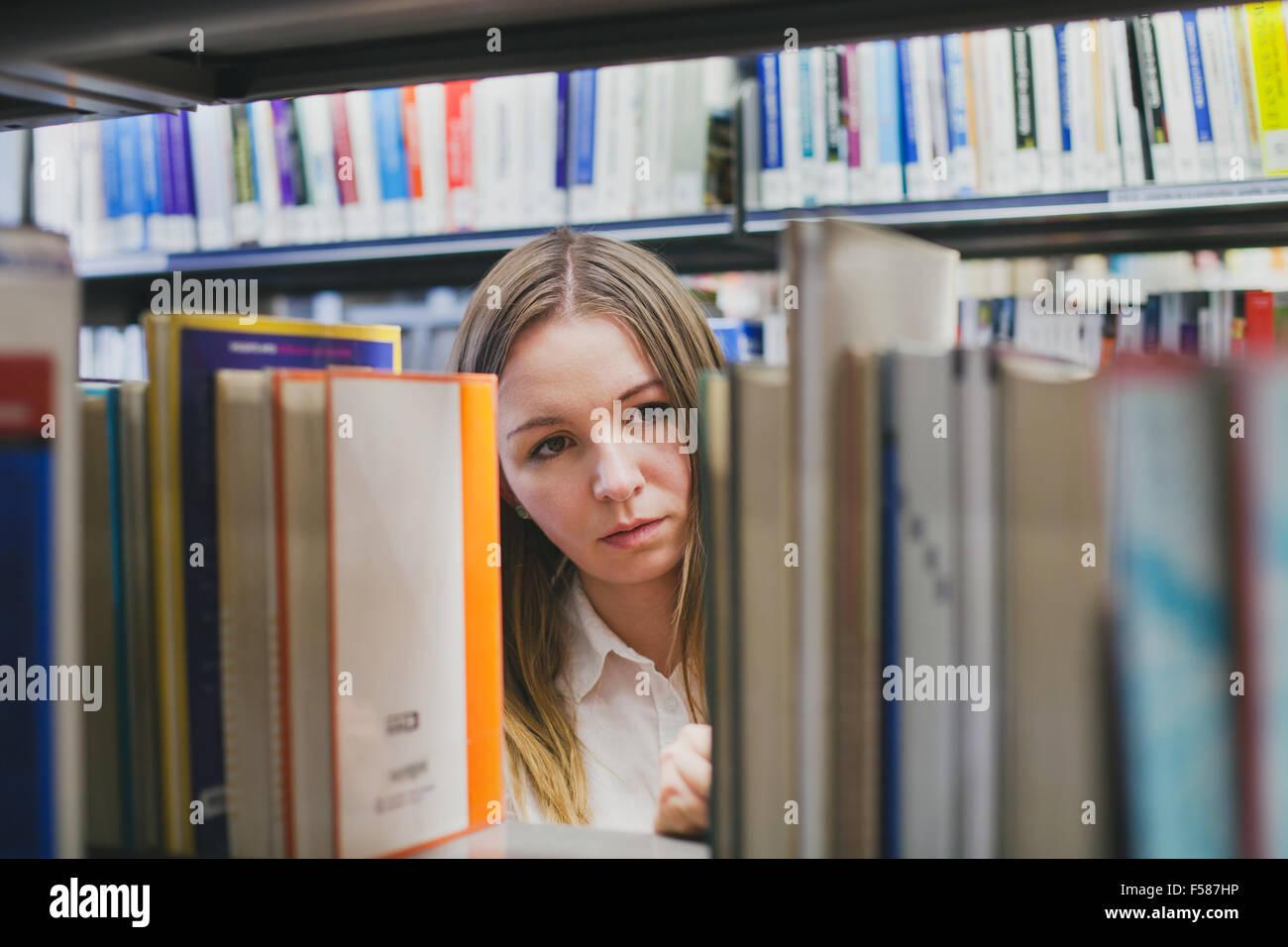 Le choix d'étudiants fille livre dans la bibliothèque Photo Stock