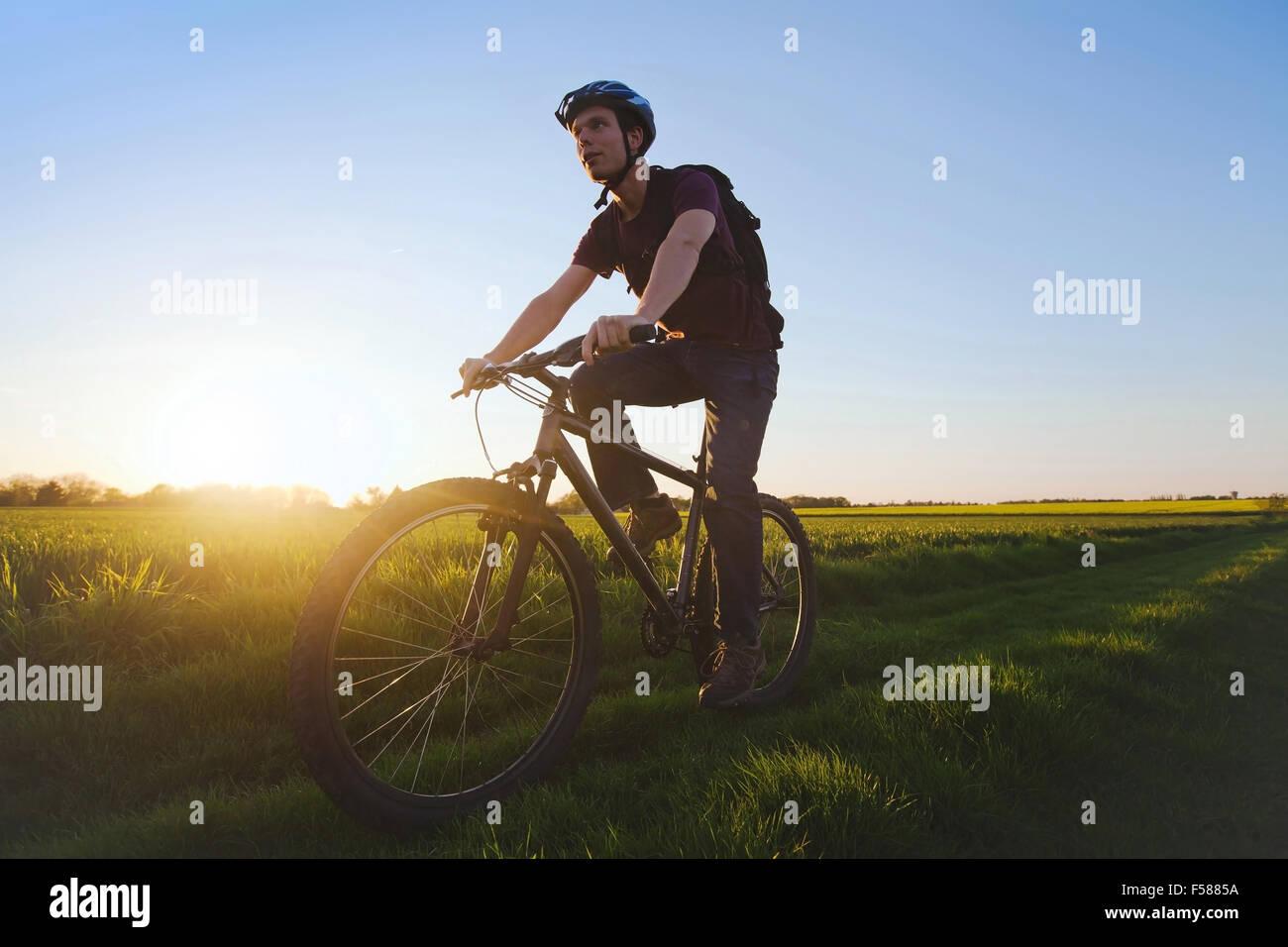 Jeune homme sportif équitation location en plein air au coucher du soleil Photo Stock