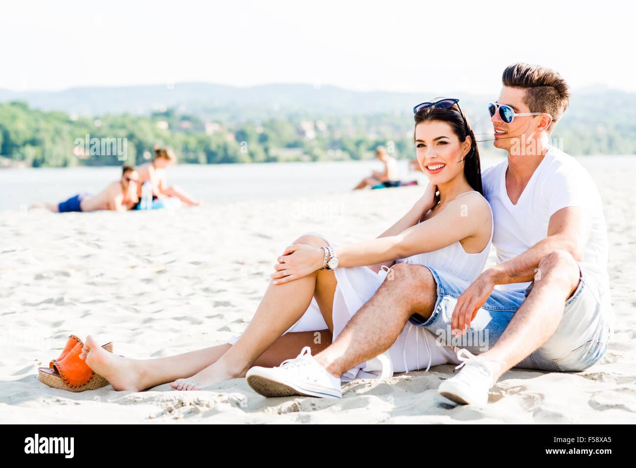 Couple amoureux assis à une plage de sable fin et souriant Photo Stock