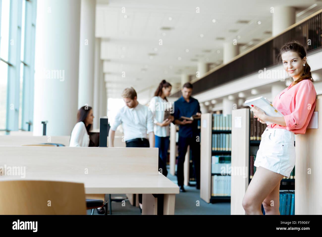 Un groupe d'universitaires qui étudient dans la bibliothèque et la conversation dans un esprit positif Photo Stock