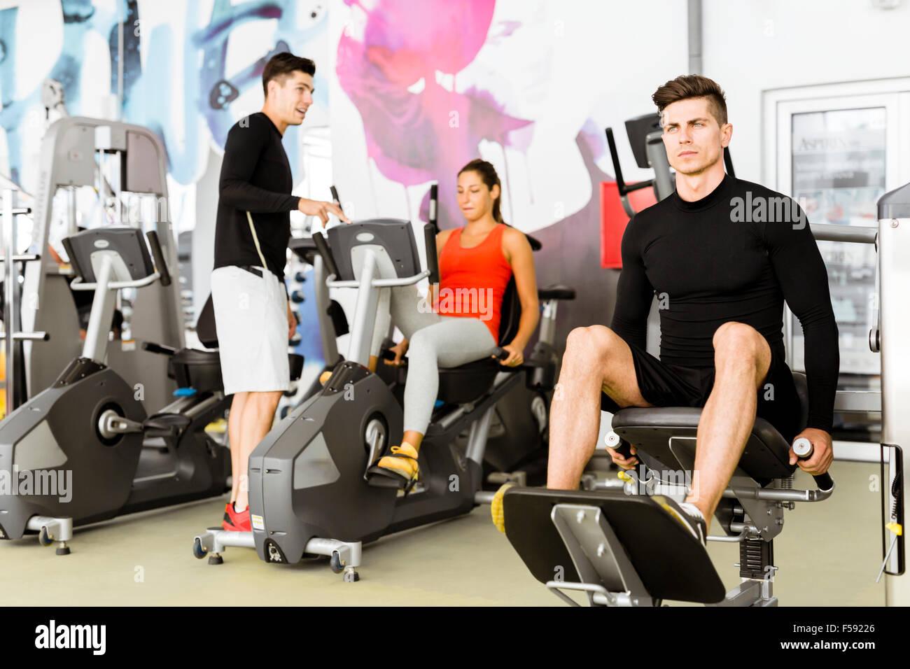 Groupe de jeunes gens qui travaillent ensemble dans une salle de sport Photo Stock