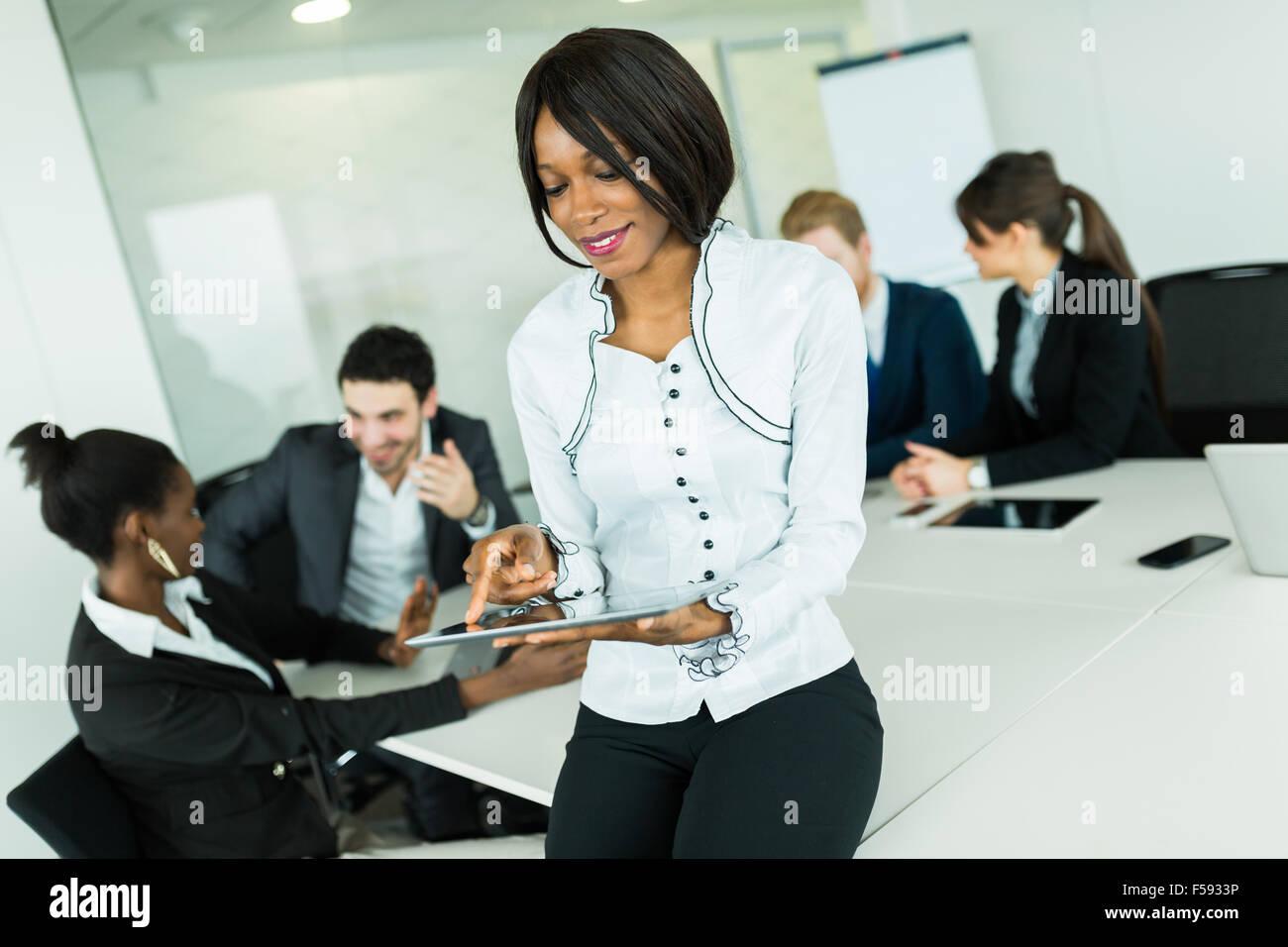 Belle, jeune, noir, femme d'Afrique à l'aide d'un comprimé à une réunion de bureau Photo Stock