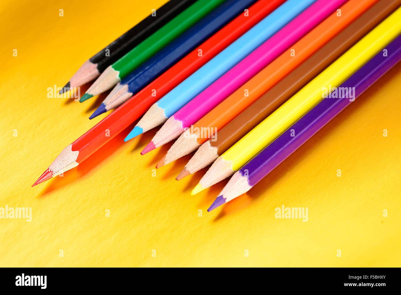 Crayons de couleur avec différentes couleurs sur fond doré Photo Stock