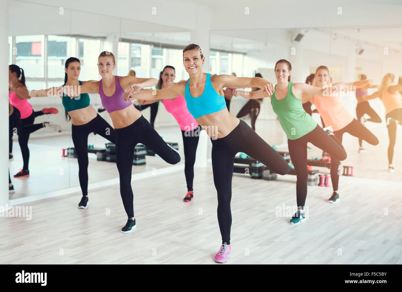 grand groupe de mettre en place des jeunes femmes travaillant dans une salle de sport faire des