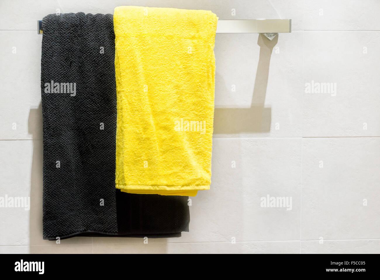 Serviette jaune et noir sur le crochet dans la salle de bains Banque ...
