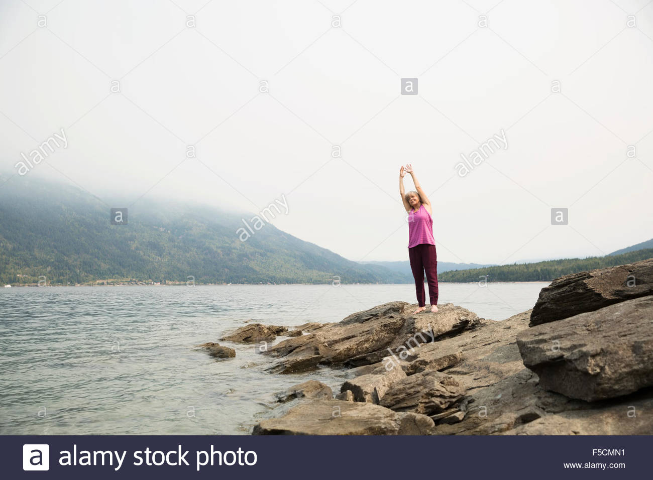 Mature Woman practicing yoga on rock at lakeside Photo Stock