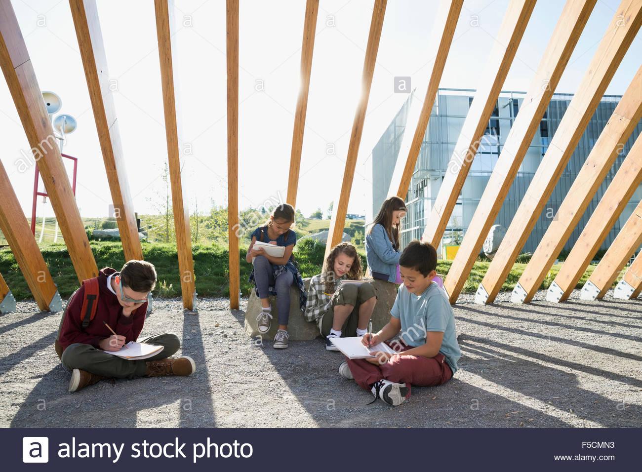 Les élèves à faire leurs devoirs en vertu de poutre en bois de ronde Photo Stock