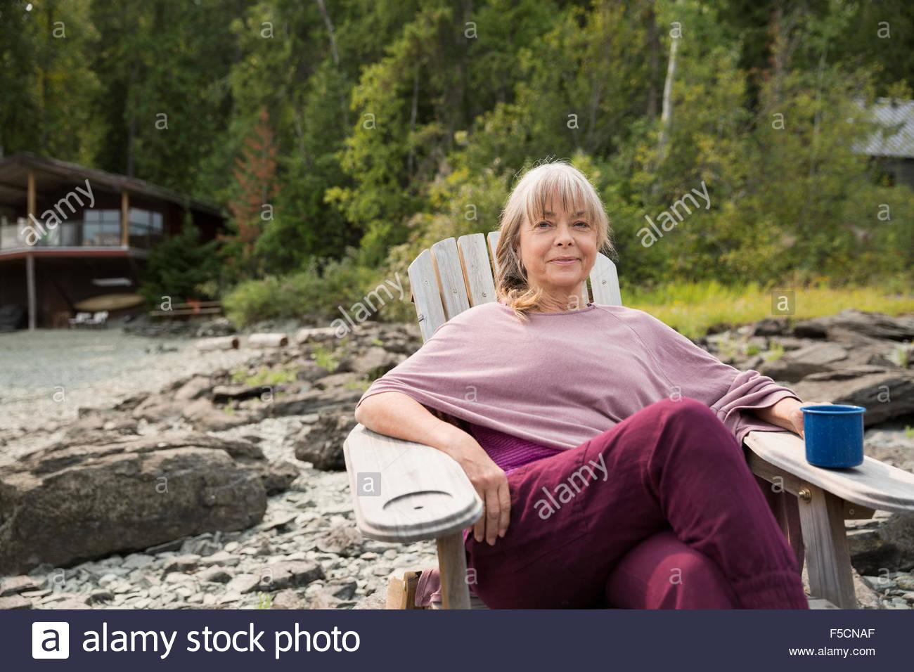 Portrait of smiling woman drinking coffee en dehors de cabin Photo Stock