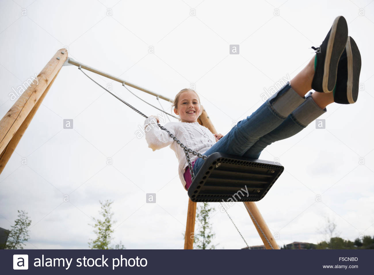 Portrait of smiling girl swinging à jeux pour enfants Photo Stock