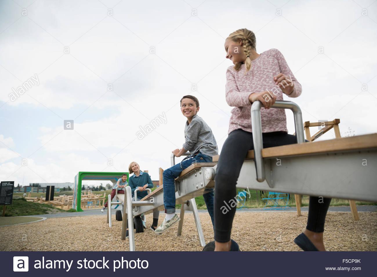 Les enfants jouant sur la balançoire à jeux pour enfants Photo Stock