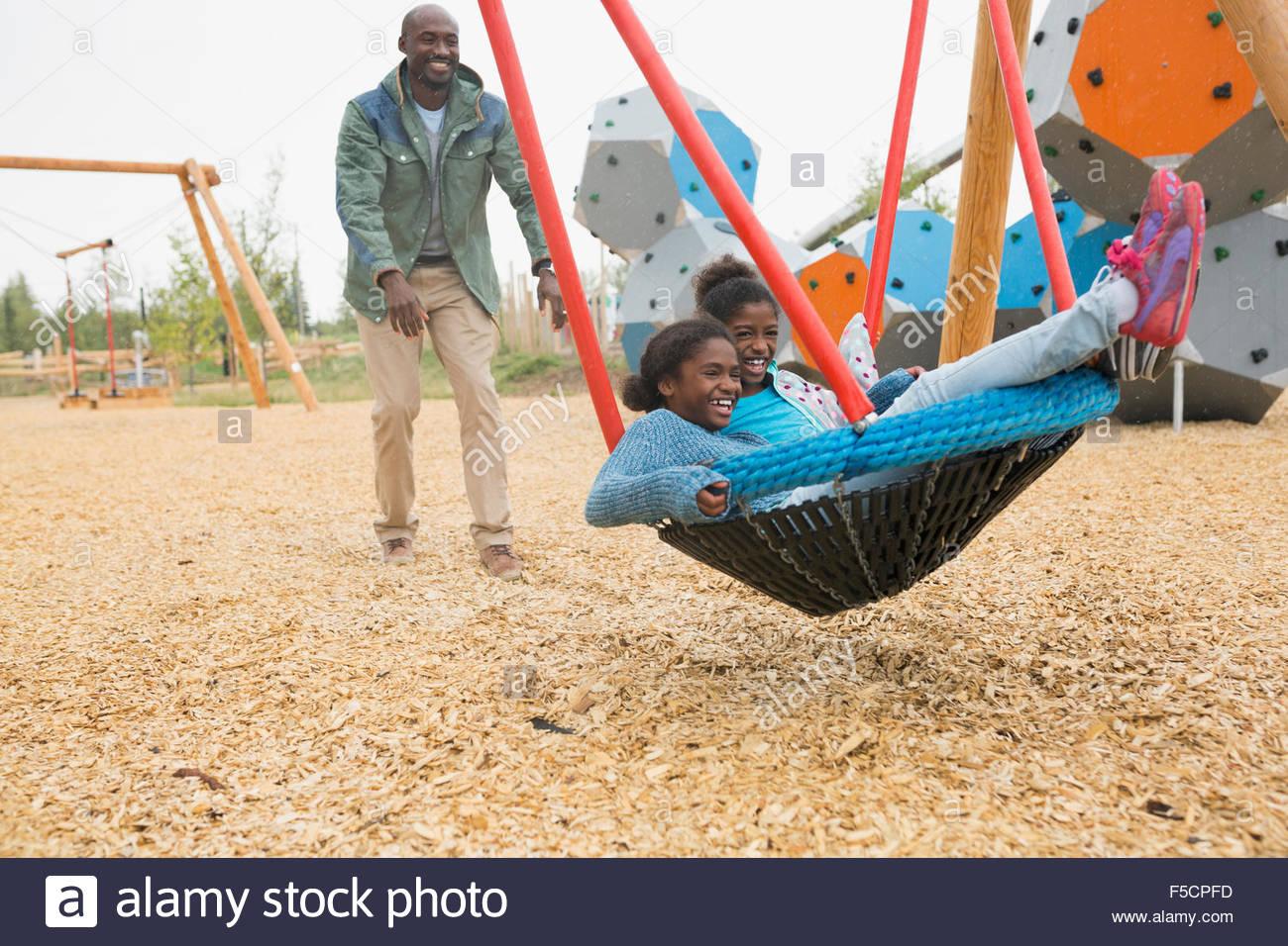 Père poussant leurs filles en swing au net jeux pour enfants Photo Stock