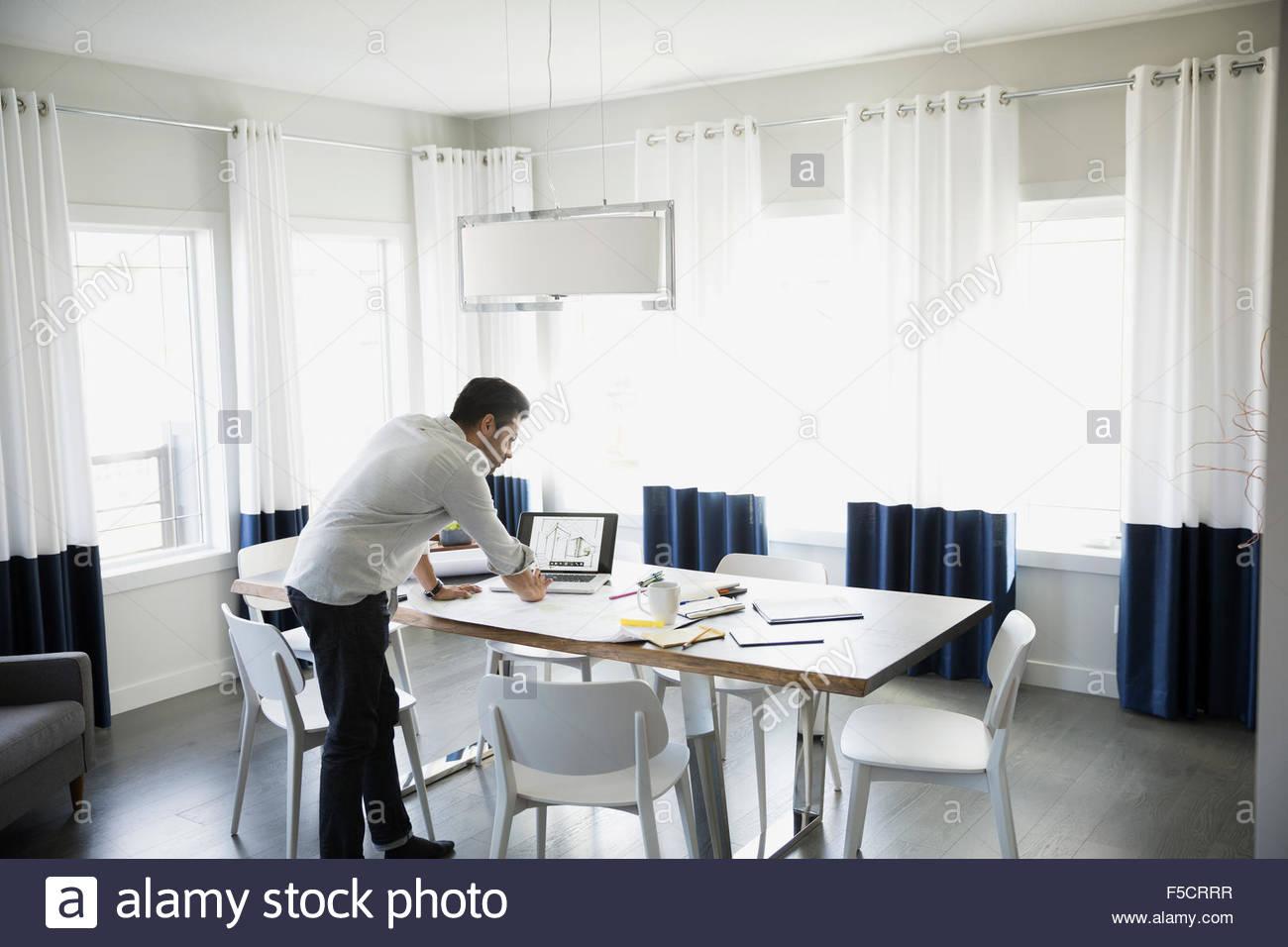 Architecte travaillant à l'ordinateur portable sur une table à manger Photo Stock