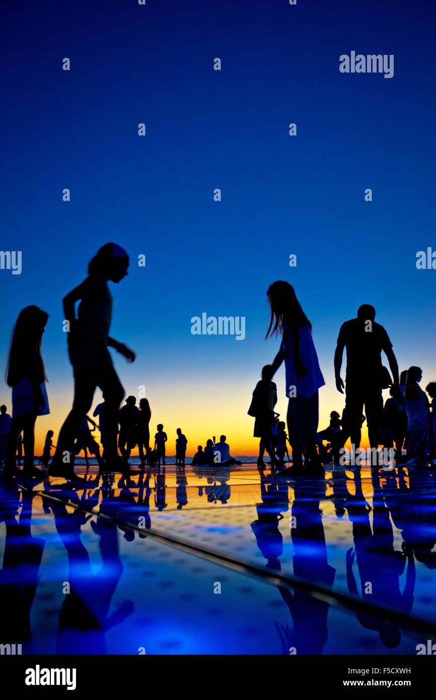 Les gens silhouette sur soleil colorés, Zadar, Croatie Photo Stock