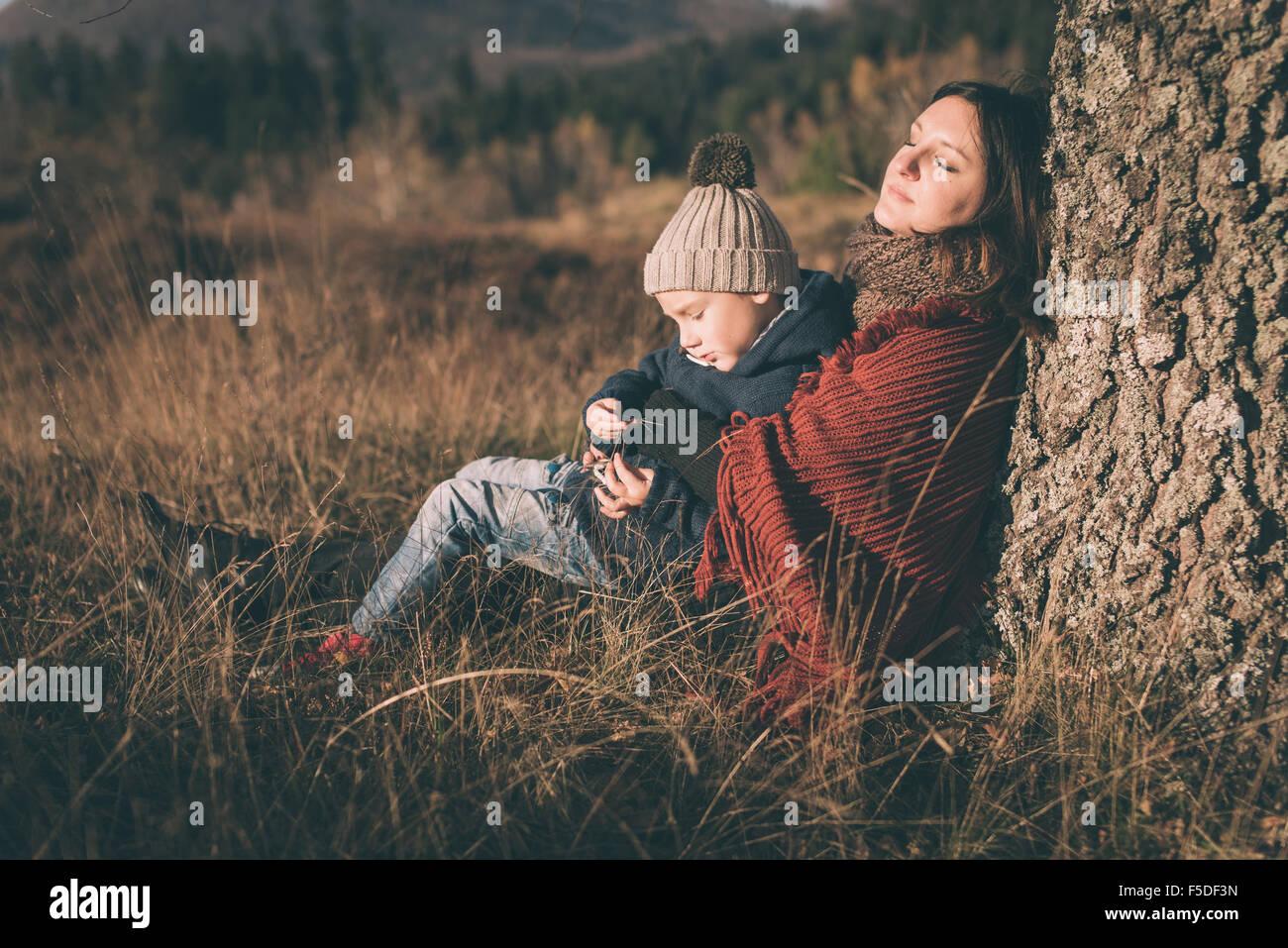 La mère et le fils assis sous l'arbre. Photo Stock